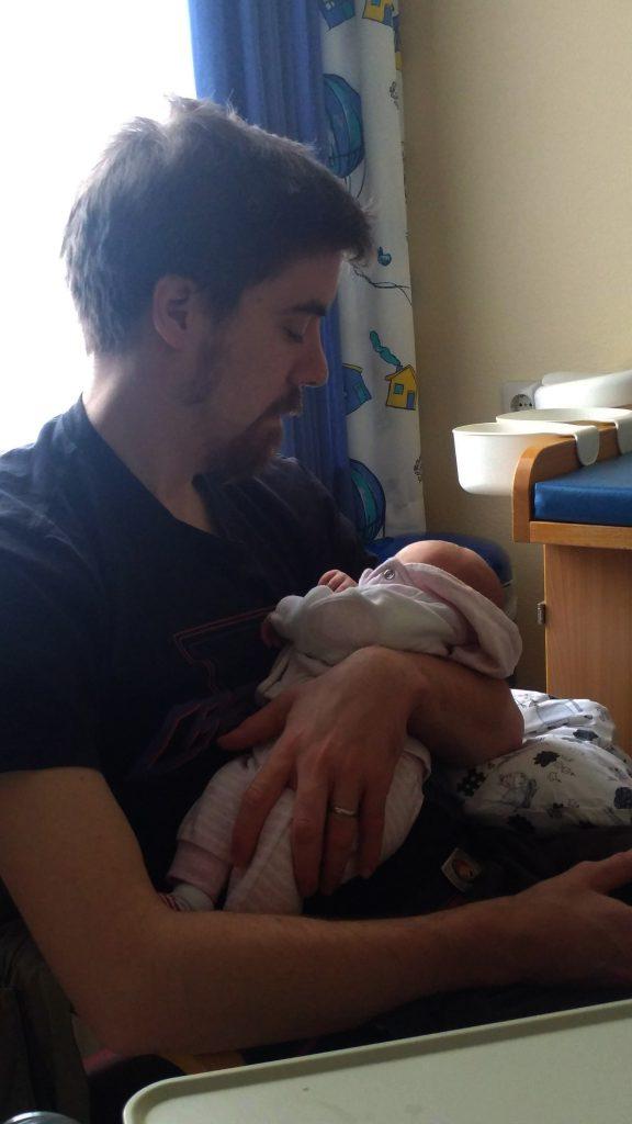 Papa Staufi mit Baby im Arm nach der Geburt